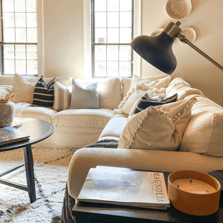 Family room sofa with fall candle and black coffee table