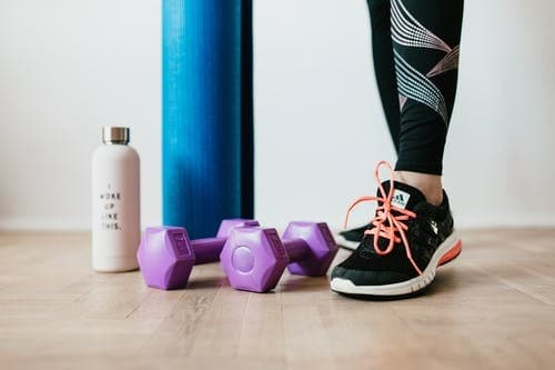 woman in black leggings and black sneakers with dumbbells and a water bottle.