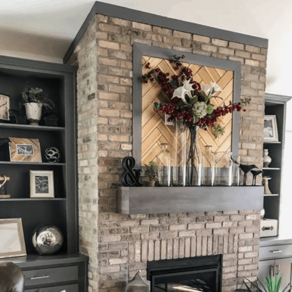 brick fireplace with wooden frames wall art with florals and jar on the mantel