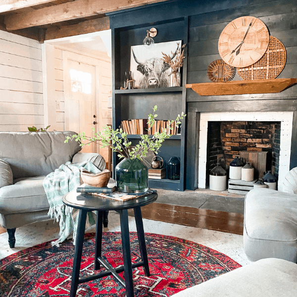 living room with dark fireplace wall and clock styled on mantel
