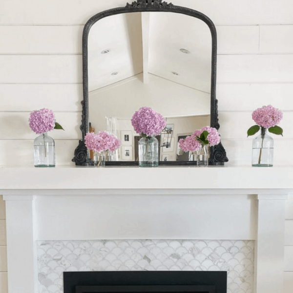 white fireplace mantel with pink flowers in glass jars.