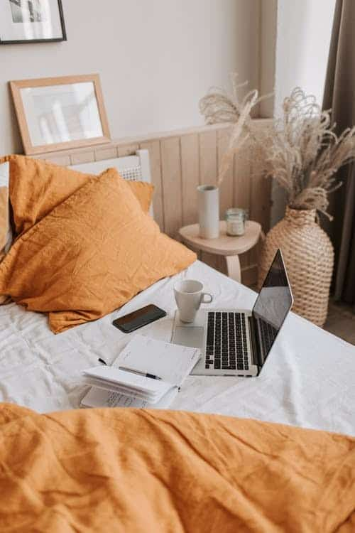 computer sitting on bed with orange bedding