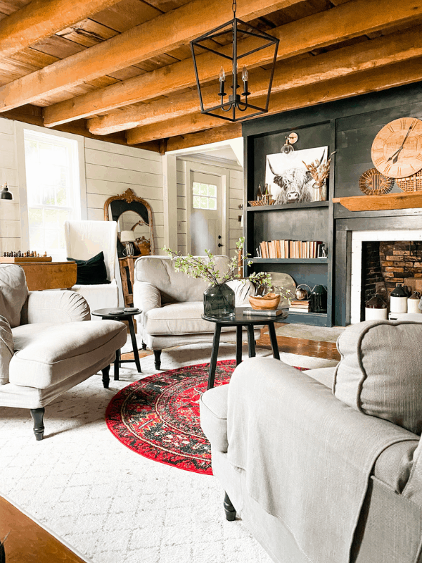 Boho farmhouse living room with dark fireplace surround and shiplap on walls.