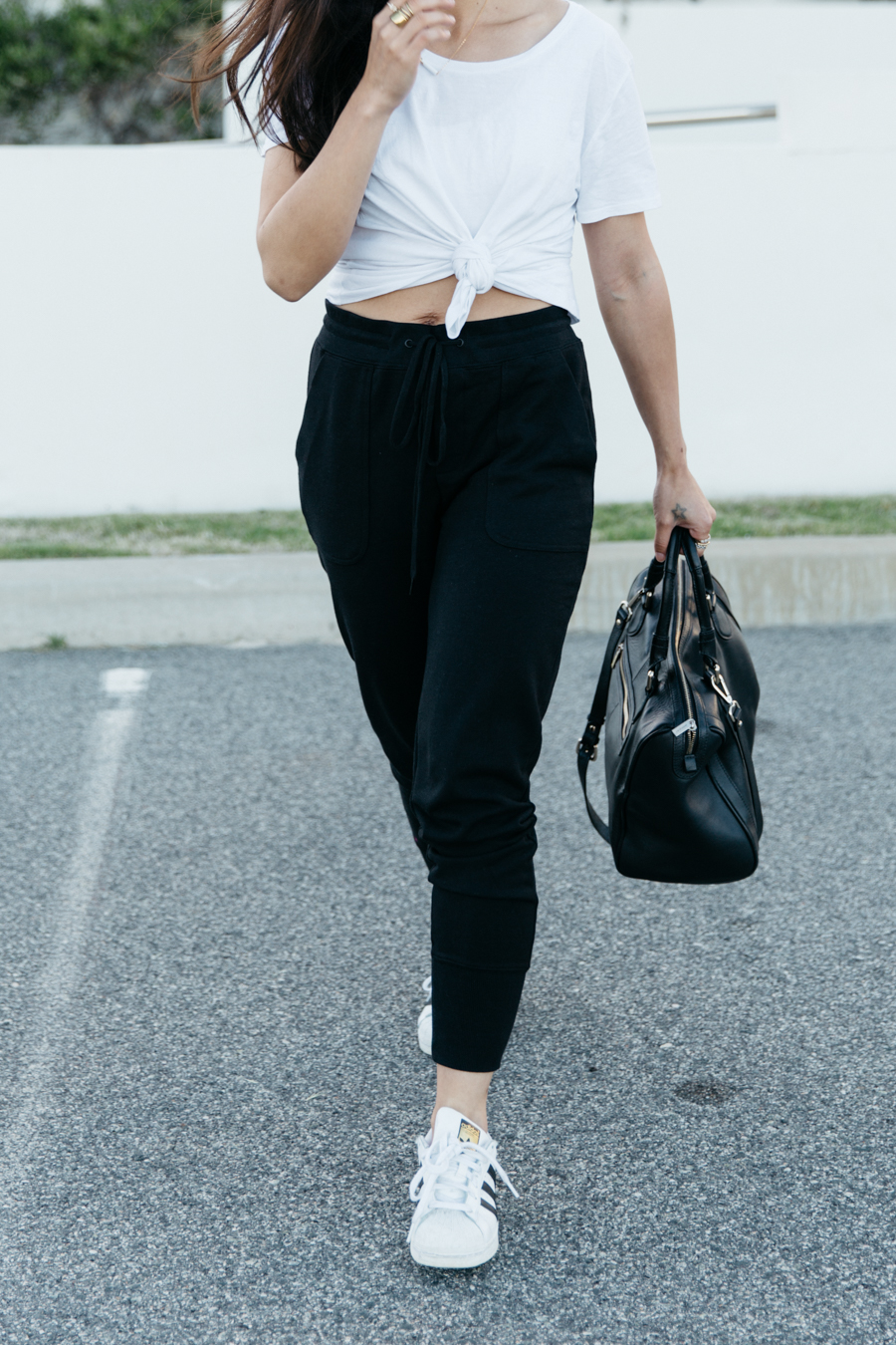 Casual sweat pants outfit with white knotted t-shirt & black leather bag & sneakers.
