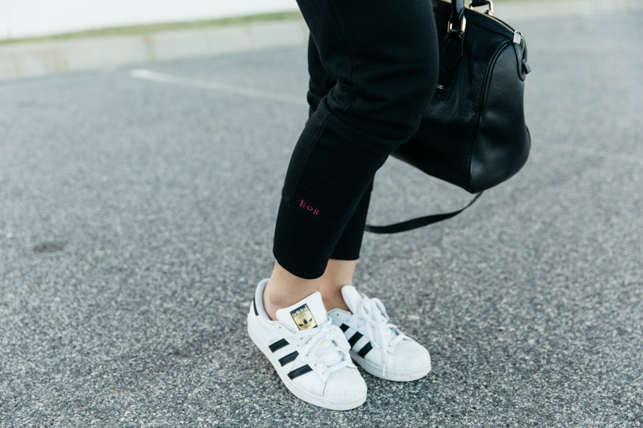 Adidas Superstars sneakers with black sweat pants.