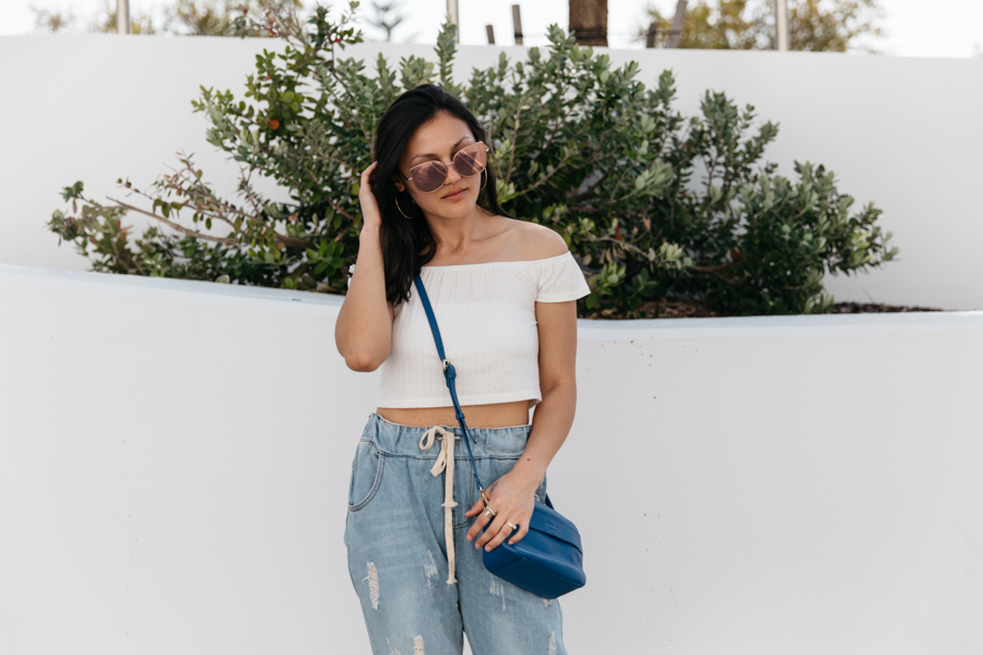 White cold shoulder crop top with drawstring boyfriend jeans. Perth street style.