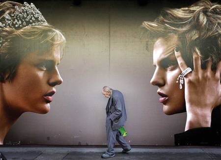 An elderly man walks past an advertisement for a new luxury store in the Central district of Hong Kong