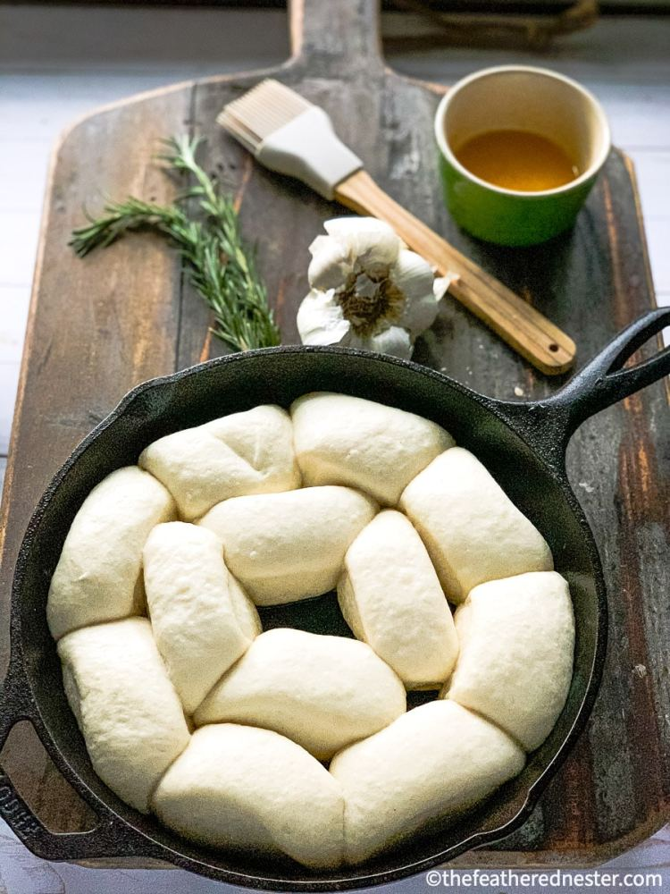 cast iron skillet with dinner rolls ready to brush with rosemary and garlic butter