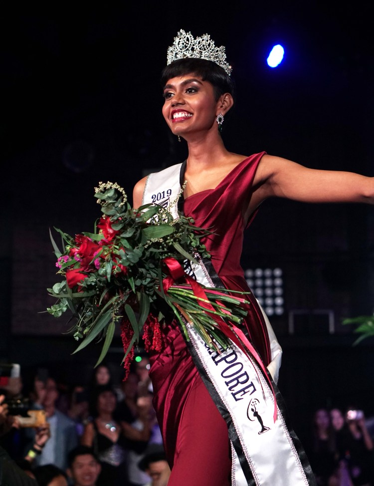 Mohana walking down the aisle with a bouquet for flower after being crowned Miss Universe Singapore 2019