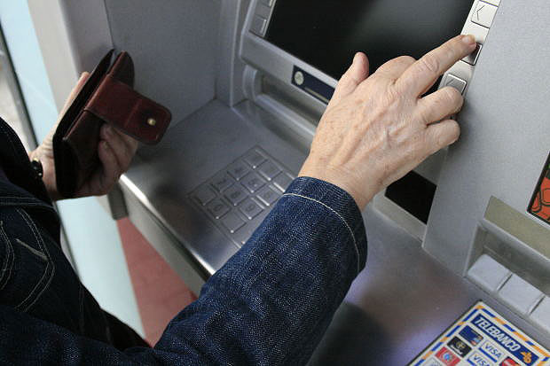 Image of ATM withdrawl to represent collecting or making alimony payments