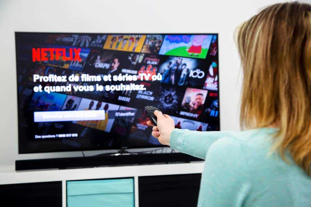 Woman turning her tv on to the streaming service Netflix.