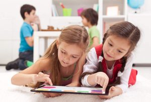 Two little girls playing on a tablet computing device in a playroom - laying on the floor