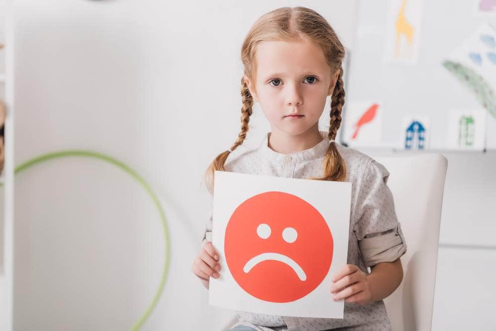 Young Girl with blonde har and braids holding a red sad face photo.