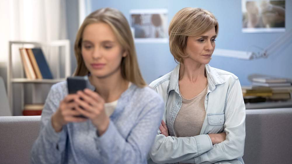 Daughter with smartphone in hands ignoring her mom, indifference, puberty age