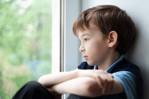 sad little boy looking out of the window with his arms crossed