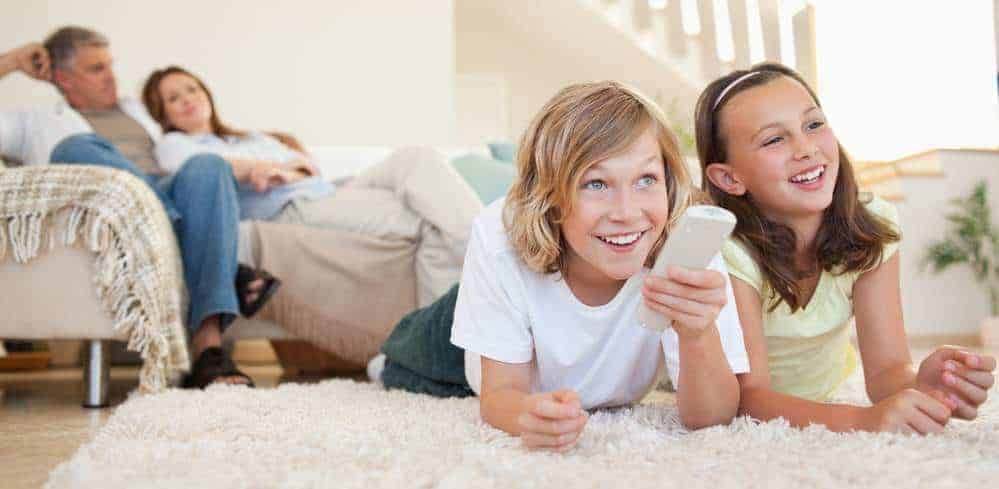 Siblings lying on the floor watching tv together with parents on the sofa in the background.