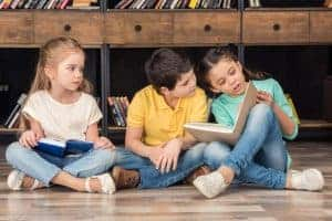 three children sitting on the floor and reading books together