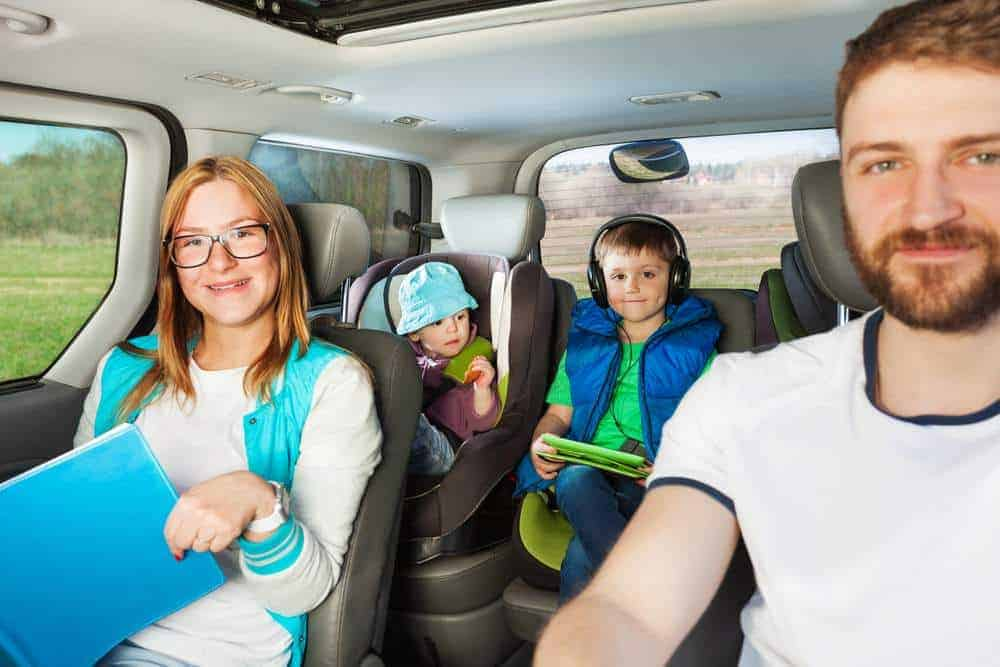 Close-up portrait of family travelling by car with boy listening to an audiobook