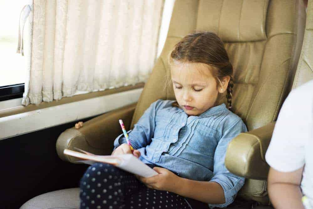 girl sitting in an RV chair writing in a book