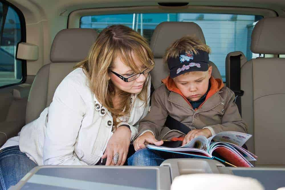 mother and her son are reading a book on a backseat of a car