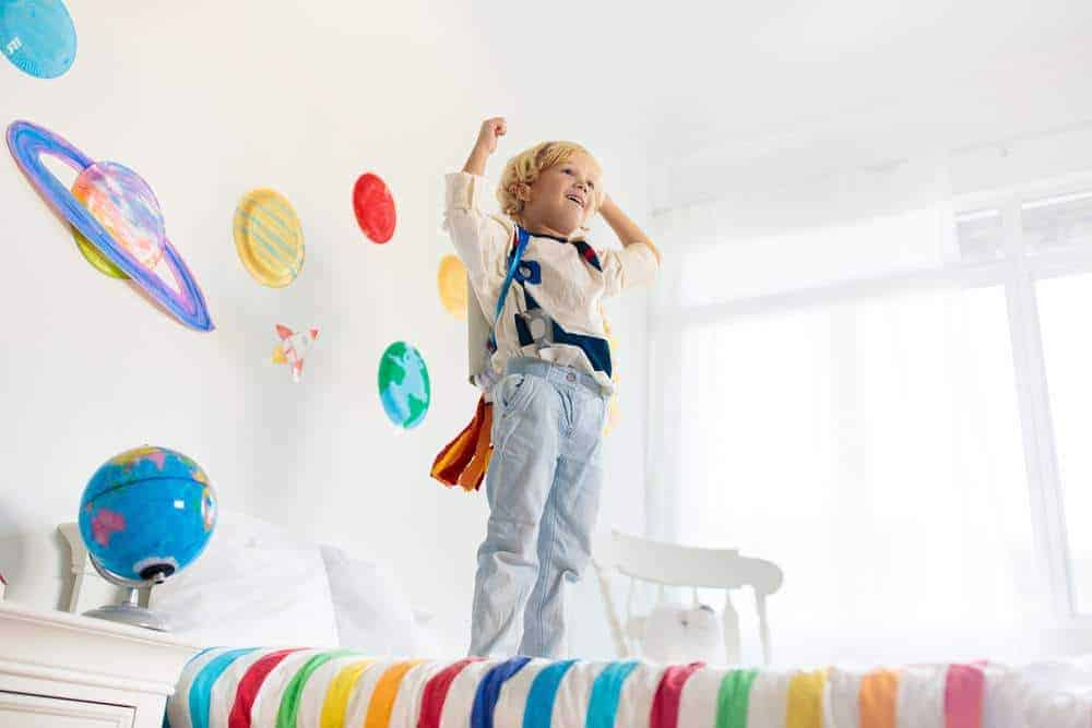 Kids play astronaut. Little boy in space costume jumping on bed with rocket. Solar system and planet room decoration. Creative child, future profession.