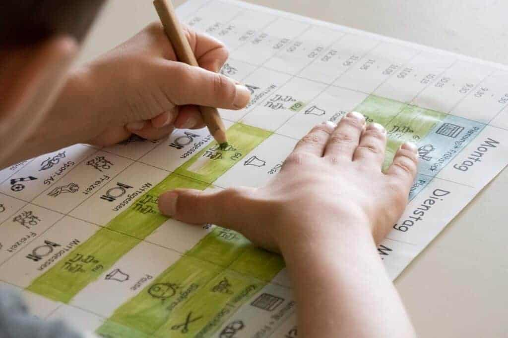 A Pupil coloring a time table, showing his new daily homeschool routine