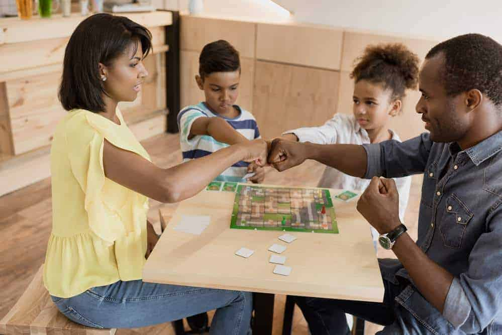 Mom and dad playing a board game with kids