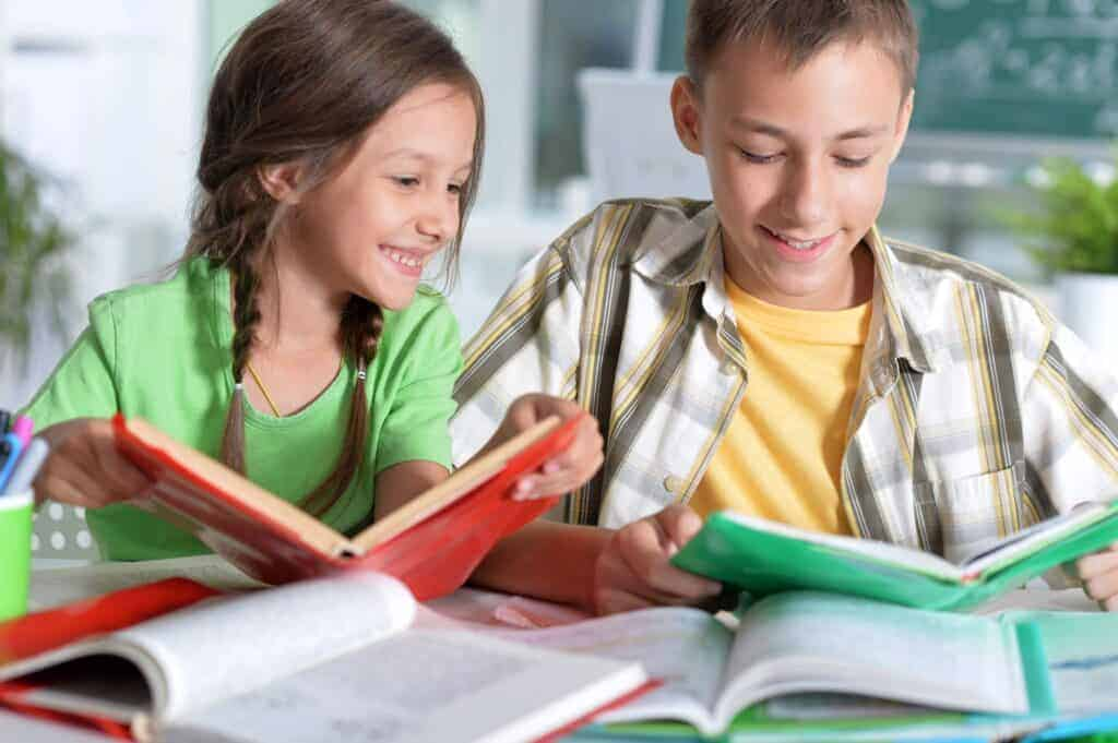 brother and sister looking at books together and studying