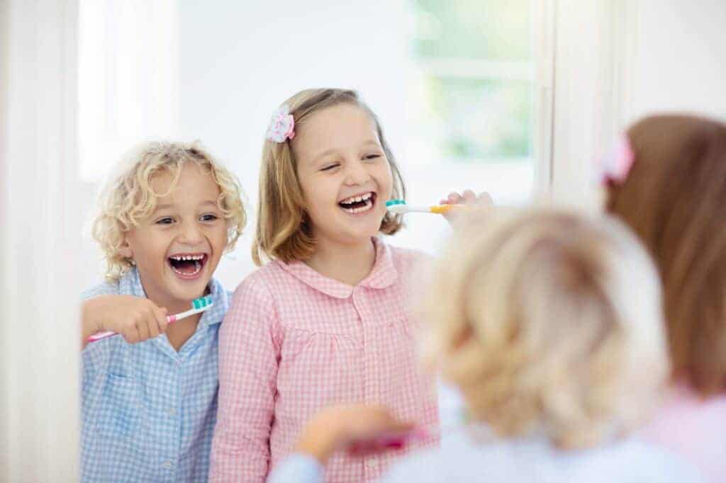 Child brushing teeth. Kids with toothpaste and brush. Dental and oral hygiene, care. Healthy daily routine for children. Kid after shower or bath at home. Girl and boy in pajamas with tooth paste.