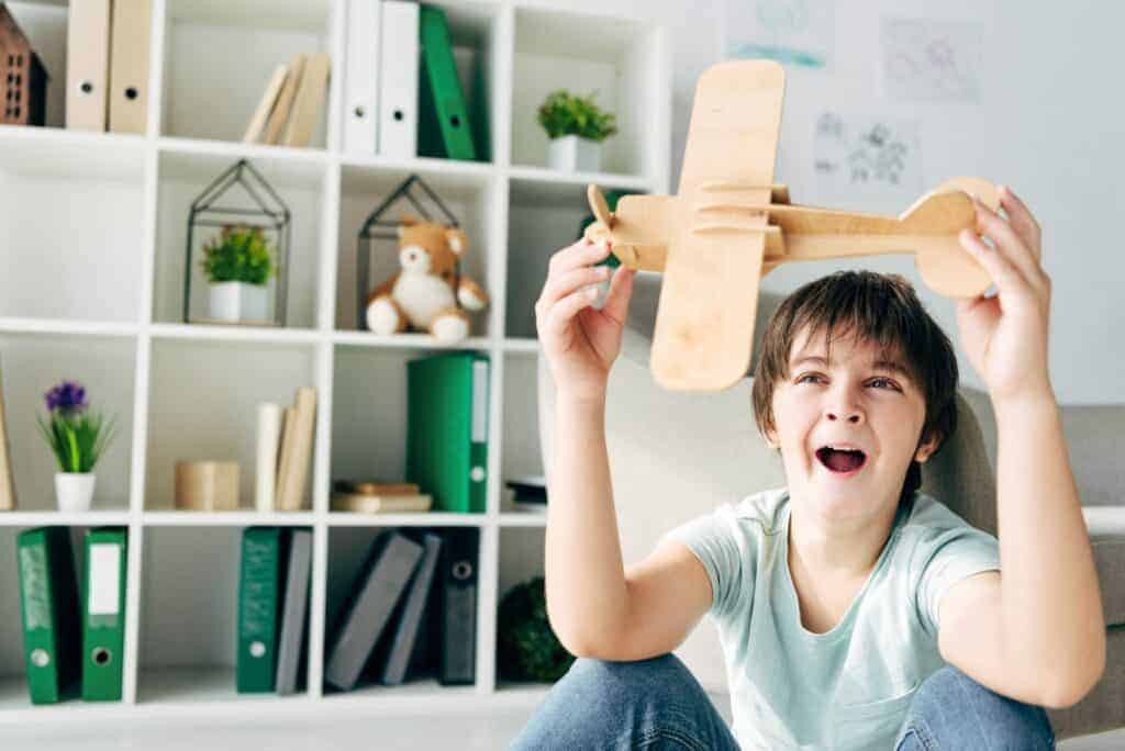 boy playing with wooden airplane, yawning. Homeschool organization in background