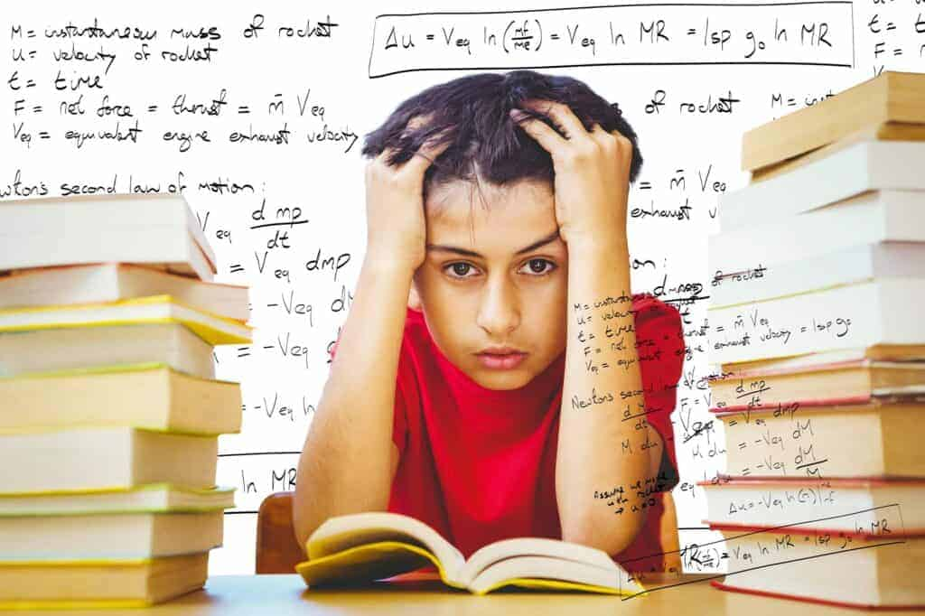 Tensed boy sitting with stack of books against rocket science theory