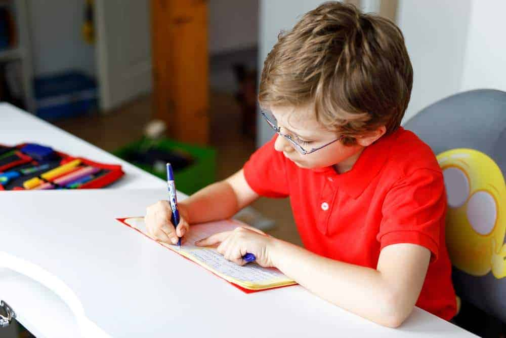Cute little kid boy with glasses at home making homework, writing letters with colorful pens. Little child doing exercise, indoors. Elementary school and education, imagine fantasy concept.