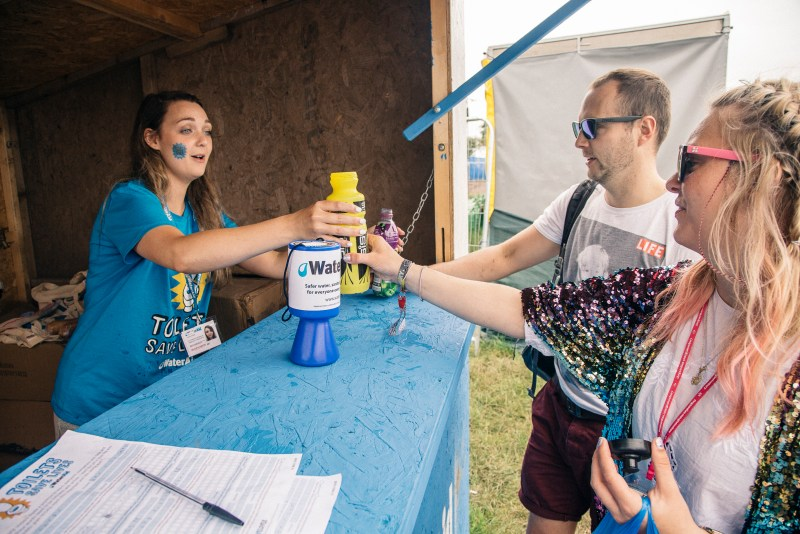 A WaterAid volunteer refilling a water bottle at Glastonbury
