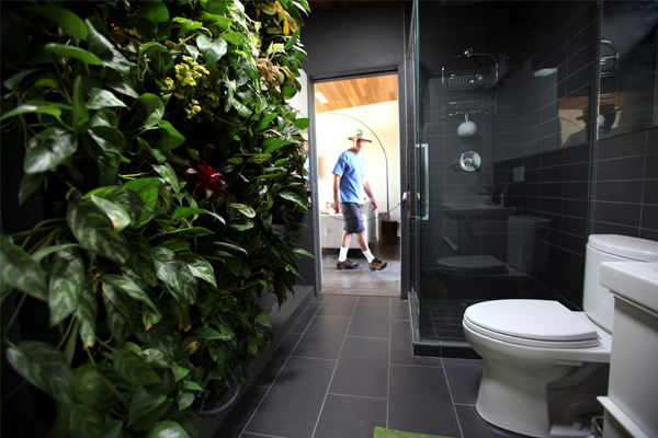 Ken Bernstein looks inside Team Alberta's bathroom, which features a living wall that hosts plant life for cooling, air purification, and connection to nature throughout the year at the Solar Decathlon 2013 on October 5, 2013 at Orange County Great Park in Irvine, Calif.  image: Stefano Paltera/U.S. Department of Energy Solar Decathlon