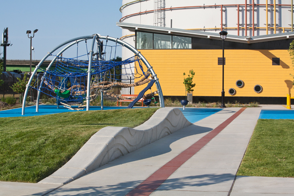 Wave-like forms and an industrial aesthetic relate play equipment to the water infrastructure in Jerome D. Barry Park, a neighborhood park in West Sacramento, CA, designed by Callander Associates. image: Billy Hustace