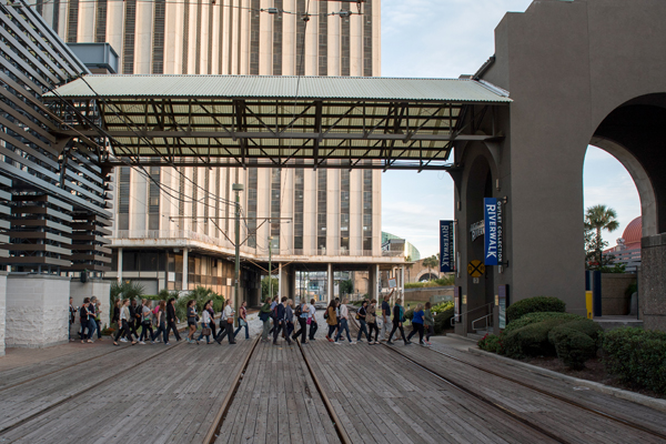 After hearing an overview of the history and plans for the Edward Durell Stone-designed former World Trade Center building set to become a Four Seasons Hotel (in the background), the WILA Walk crosses the railroad tracks to reach the Riverwalk and Spanish Plaza. image: Event Photography of North America Corporation (EPNAC)