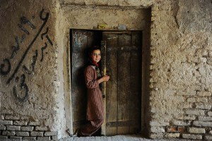 Image Source: seair21, Flickr, Creative Commons A girl stands in the doorway of her house in the old sector of Herat