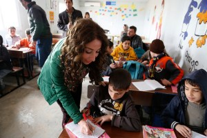 Image Source: DFID - UK Department for International Development, Flickr, Creative Commons A Lebanese teeacher lends a hand to Syrian children in Zaatari, Jordan