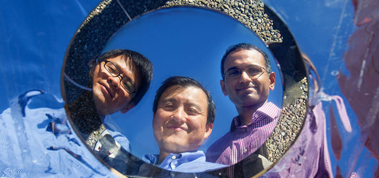 Stanford Professor Shanhui Fan, centre, gazes into the pizza- sized prototype with co-authors Linxiao Zhu, left, and Aaswath Raman, right. The high-tech mirror reflecting their faces beams heat directly into space.