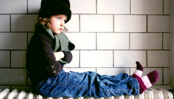 cold rental property childing sitting on heater.jpeg