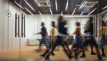 Group of office employees at coworking center. Business people walking at modern open space. Motion blur. Concept
