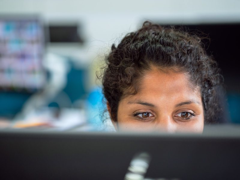 woman's face behind computer screen