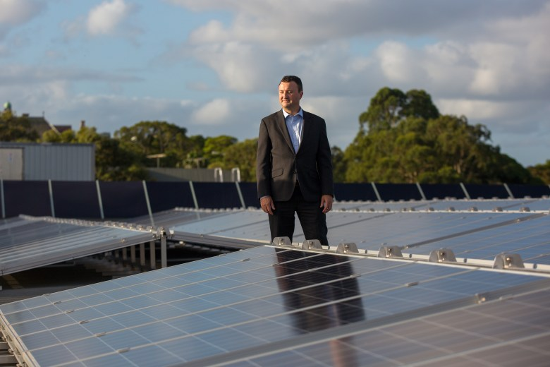man in suit standing with solar panels