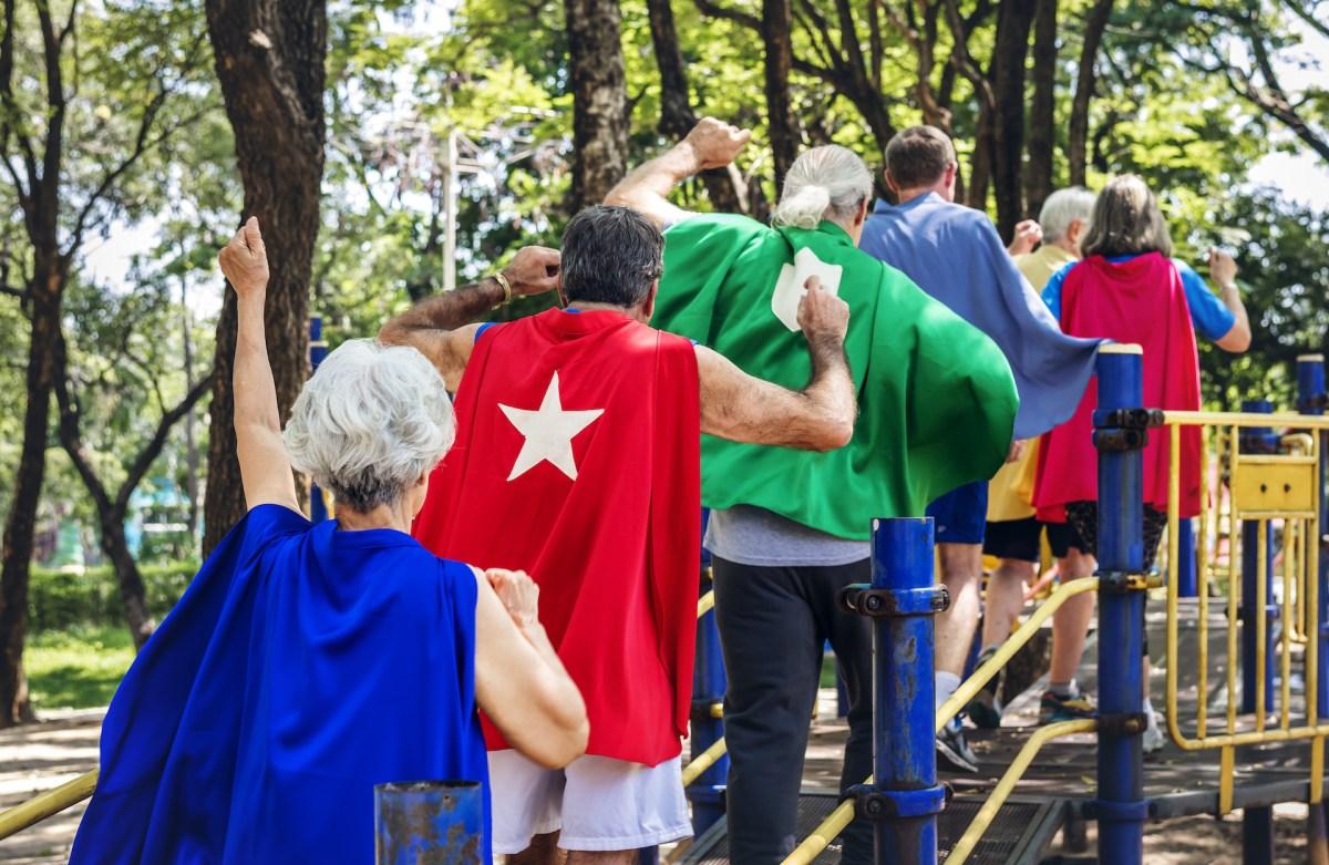 Happy seniors wearing superhero costumes at a playground