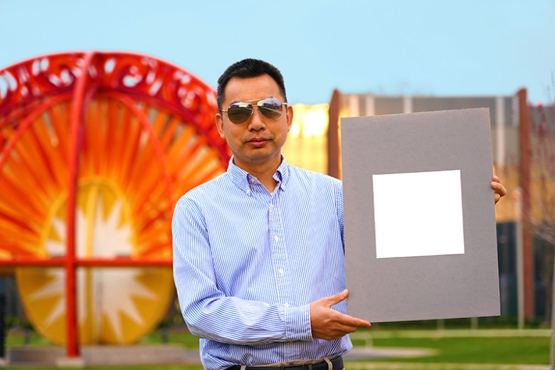 Xiulin Ruan, a Purdue University professor of mechanical engineering, holds up his lab's sample of the whitest paint on record. (Purdue University/Jared Pike)