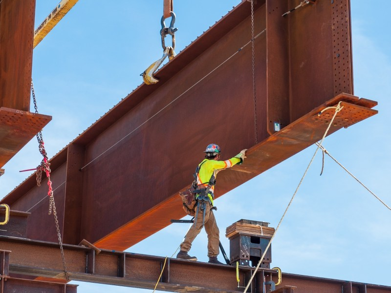 Steel worker positioning a steel girder with 3 meter wide flange on temporary supports to bolt in the next section of bridge girder.