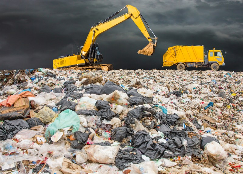 garbage dump pile in trash dump or landfill,backhoe and truck is dumping the gabage from municipal,garbage dump whit old garbage truck and dark clouds or rain clouds