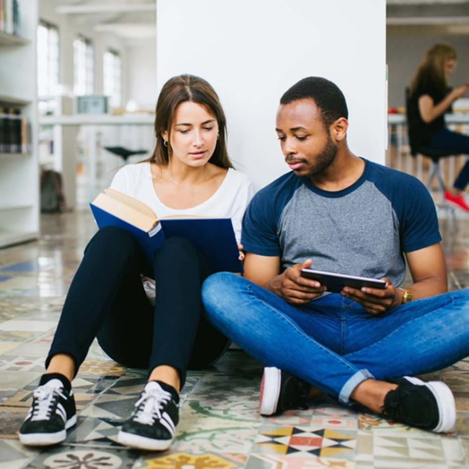 a man and woman sitting on the floor in the library studying