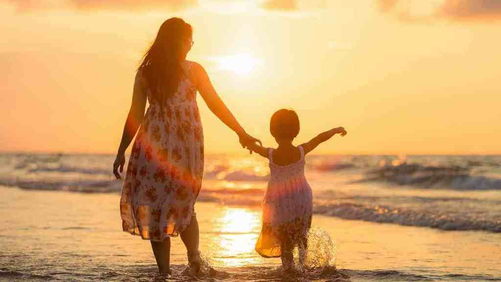 a woman on holiday with her daughter after investing her tax refund to build wealth