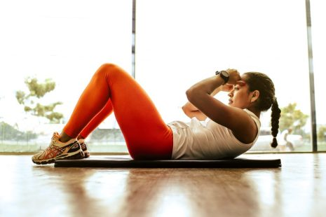 Image of woman doing body crunches to illustrate fitness